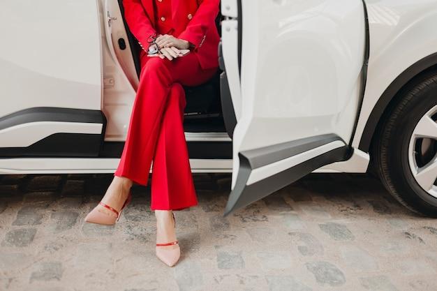 Schließen sie oben beine in den fersen und in den händen, die telefon der schönen sexy reichen geschäftsartfrau im roten anzug halten, der im weißen auto aufwirft