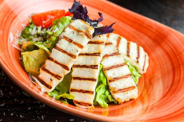 Schließen sie oben caesar salat gegrillte hähnchenbrust, frischer salat in einem teller auf einem dunklen holztisch
