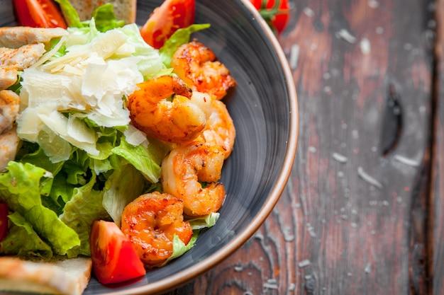 Schließen sie oben caesar salat mit hähnchen und garnelen gegrillte hähnchenbrust, garnelen, tomaten, frischer salat in einem teller auf einem dunklen holztisch