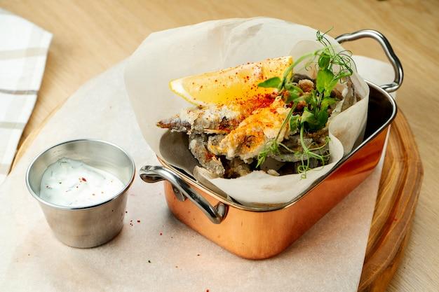 Schließen sie oben capelin frittiert in einer stilvollen portion mit weißer soße auf holzhintergrund. straßenessen. selektiver fokus. meeresfrüchte