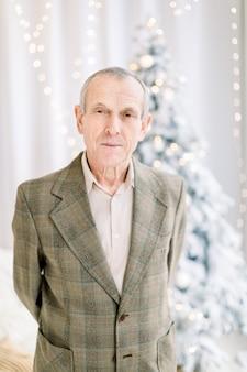Schließen sie oben des älteren mannes in der karierten jacke und im hellen hemd, die zur kamera am gemütlichen raum zu hause über weihnachtsbaumhintergrund aufwerfen