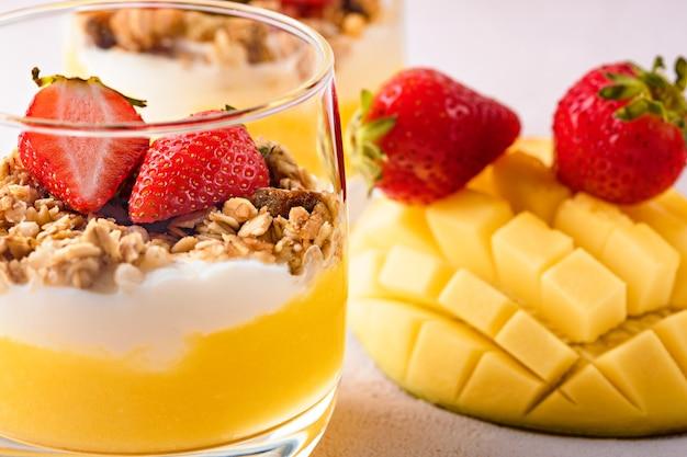 Schließen sie oben dessert mit ricotta-käse, mango, müsli und erdbeeren auf rosa hintergrund. tropisches dessertkonzept