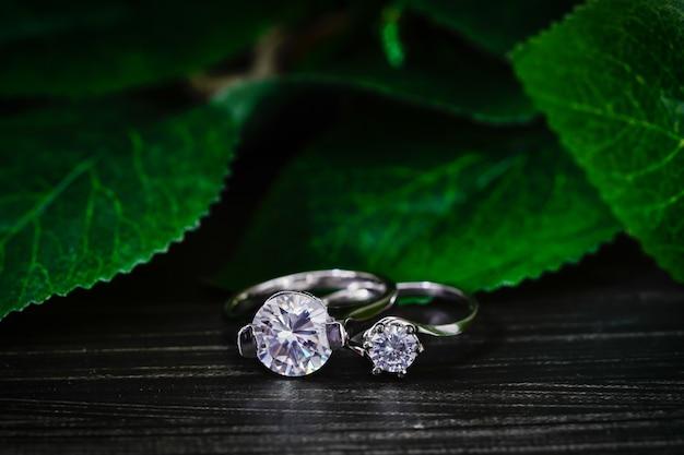 Schließen sie oben diamant edelstein eheringe mit grünen blättern auf schwarzem hintergrund