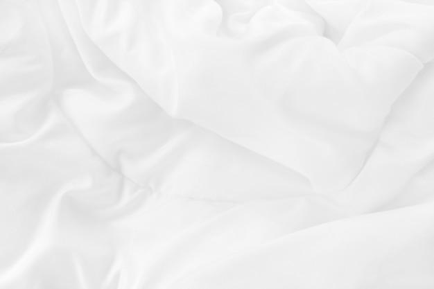 Schließen sie oben draufsicht des weißen bettlakenes und der faltigen unordentlichen decke im schlafzimmer nach dem aufwachen am morgen.