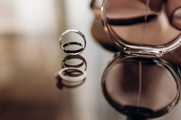 Schließen sie oben eheringe goldringe mit parfüm auf einem glastisch. hochzeitsvorbereitung.