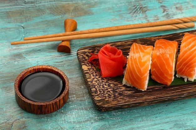Schließen sie oben einen satz von sechs sushi-rollen mit rohem lachs, der auf palmenholzteller auf blauem tisch serviert wird, blickwinkel