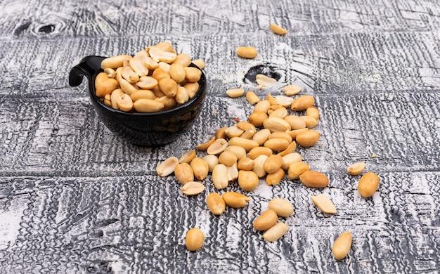 Schließen sie oben erdnüsse in der schüssel auf hölzernem grau horizontal