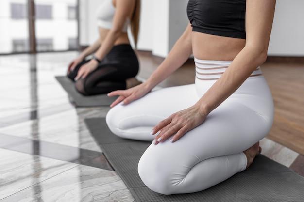 Schließen sie oben frauen auf yogamatten