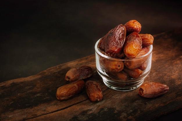 Schließen sie oben früchte der dattelpalme auf schreibtisch. getrocknete dattelpalmenfrüchte oder kurma