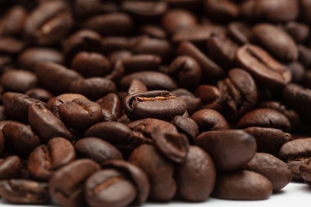 Schließen sie oben geröstete kaffeebohnen mit kopienraum. makro. tapete mit frischen kaffeekörnern. guten morgen. café.