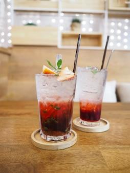 Schließen sie oben glas glas erdbeersaft mit soda auf holzuntertasse über holztisch am abendessen restaurant