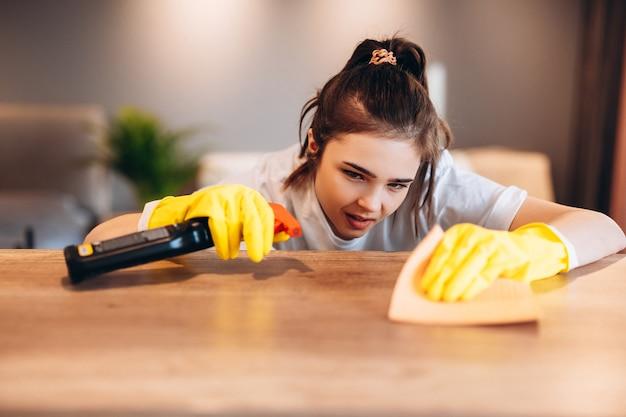 Schließen sie oben glückliche frau in gelben handschuhen, die tabelle zu hause küche mit waschmittel reinigen