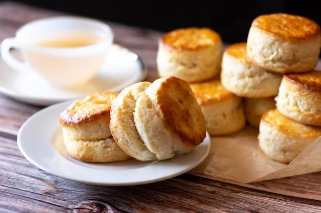 Schließen sie oben gruppe von frischen leckeren leckeren leckeren traditionellen britischen scones und einer tasse tee auf holztisch.