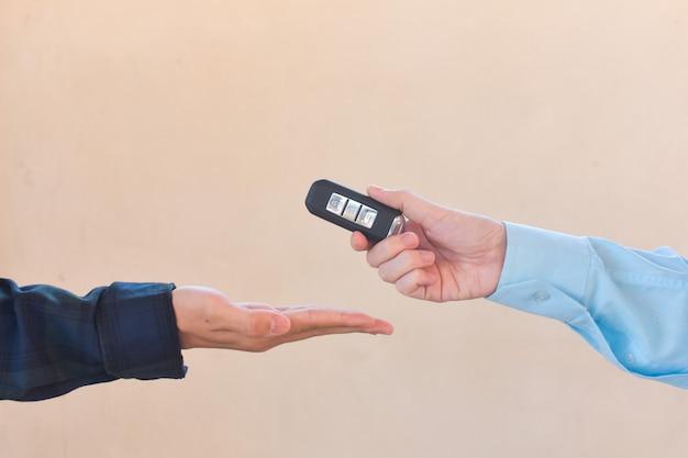 Schließen sie oben hand, die schlüsselverkaufsautokonzept hält, schlüsselauto geben und nehmen