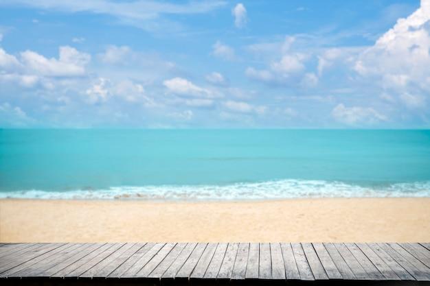 Schließen sie oben hölzerne tischplatte auf sandstrand blaues meer und tropischen strand, sommerferienkonzept.