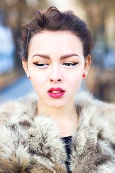 Schließen sie oben im freien modeporträt des schönen asiatischen mädchens mit der perfekten haut, die pelzjacke, das helle make-up der nadel oben und die augenlinsen trägt. herbstporträt im freien.