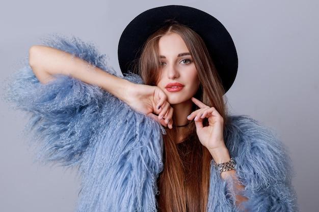 Schließen sie oben innenmodeporträt des hübschen jungen modells im stilvollen flauschigen wintermantel und im aufstellen des schwarzen hutes. abends helles make-up.