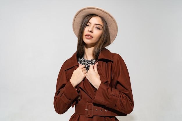 Schließen sie oben innenstudio-modeporträt der herrlichen frau im stilvollen winterbraunen mantel und im schwarzen hut