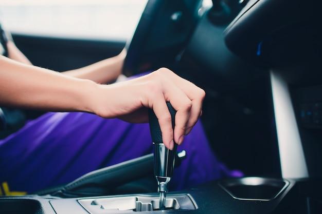 Schließen sie oben junge frau hand auf automatische gangschaltung, schaltgetriebe im auto. fahrer frau hand hält automatikgetriebe oder antrieb mit variabler geschwindigkeit im auto, schalthebel vor dem fahren auto.