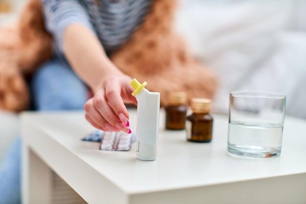 Schließen sie oben kranke junge frau, die nach einem inhalator für asthma greift