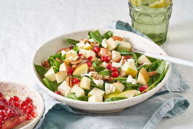 Schließen sie oben obstsalat mit nüssen, ausgewogenem essen, sauberem essen. spinat mit äpfeln, pekannüssen und feta