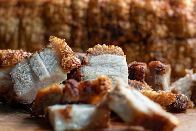 Schließen sie oben orientalischer gebratener knuspriger schweinebauch auf hölzernem schneidebrett