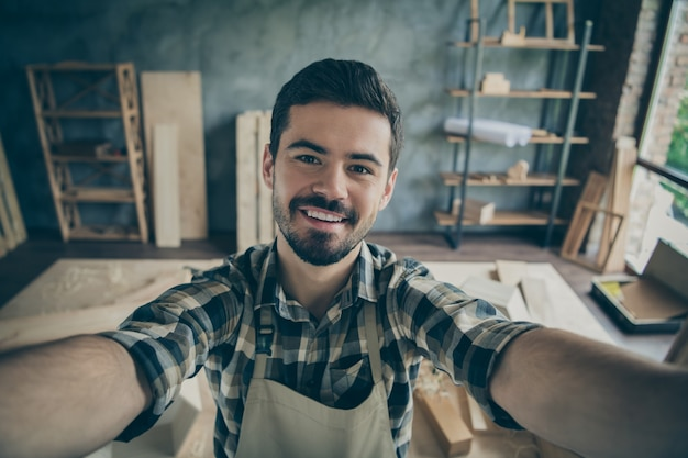 Schließen sie oben positiven vorarbeiter in haushaus garage machen selfie hartholz produktion blogging tragen kariertes kariertes hemd