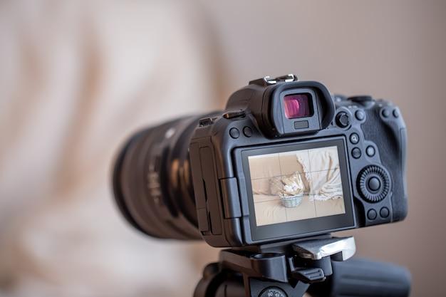 Schließen sie oben professionelle digitalkamera auf einem stativ auf einem unscharfen hintergrund. das konzept der technologie für die arbeit mit fotos und videos.