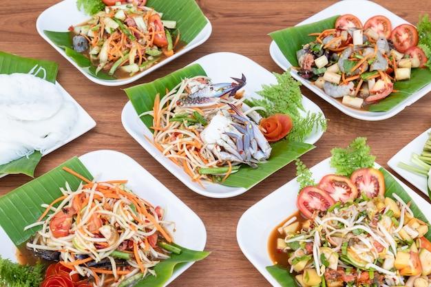 Schließen sie oben satz von mehreren papayasalat und würzigem salat auf dem tisch. lebensmittelkonzept im thailändischen stil