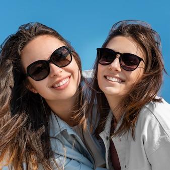 Schließen sie oben smiley-frauen mit sonnenbrille
