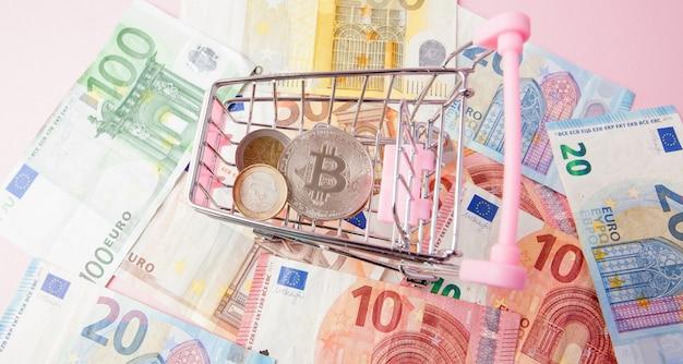 Schließen sie oben spielzeug-einkaufswagen mit bitcoin auf einer euro-oberfläche, sparen sie geld für die zukunft, ethereum-kryptowährung, blockchain-business-technologie-konzept,