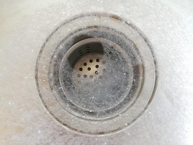 Schließen sie oben spüle abfluss und gelben schwamm reinigung metallic spüle hausarbeit konzept