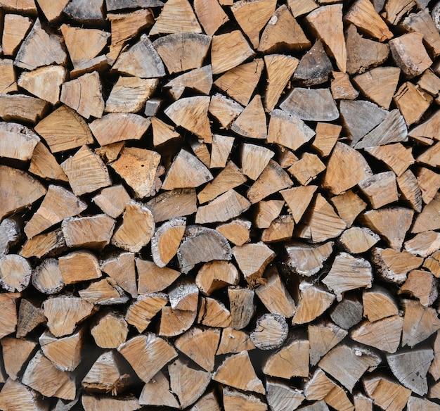 Schließen sie oben stapel von trockenen brennholz eichenholzstämmen, gehackt, gespalten und in einem stapel für winterbrennstoffvorrat, niedriger winkel, seitenansicht organisiert