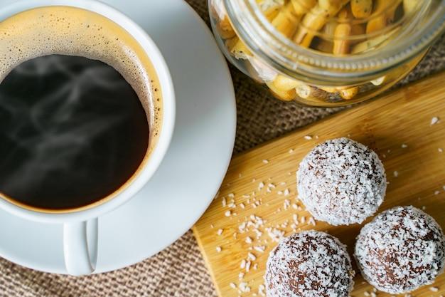 Schließen sie oben tasse schwarzen kaffee und leckere süßigkeiten mit kokosnuss auf einem holzbrett.