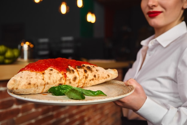 Schließen sie oben traditionelle italienische geschlossene pizza calzone auf einem teller im restaurant durch die hände der kellnerin. selektiver fokus