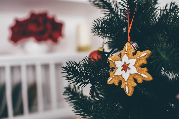 Schließen sie oben und schneiden sie ansicht der dekoration auf weihnachtsbaum in schneeflockenform. raum ist auf unscharfem hintergrund.