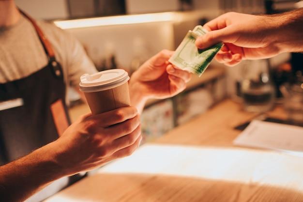 Schließen sie oben und schneiden sie ansicht einer kellnerhand, die einen tasse kaffee hält und ihn dem kunden gibt. gleichzeitig gibt ihm der kunde ein bargeld, um die bestellung zu bezahlen.