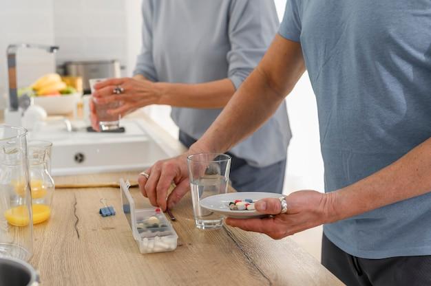 Schließen sie oben vom älteren paar, das ergänzungstablettenpillen mit dem glas des alten gesunden paares wasser hält