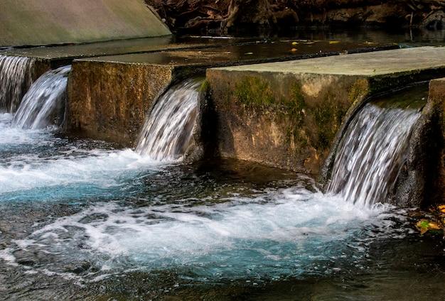 Schließen sie oben vom alten konkreten überlaufkanal im fluss am tropischen wald.
