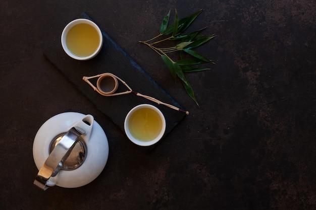 Schließen sie oben vom asiatischen teesatz des weißen porzellans mit grünem tee japan matcha auf schwarzem steinschreibtisch.
