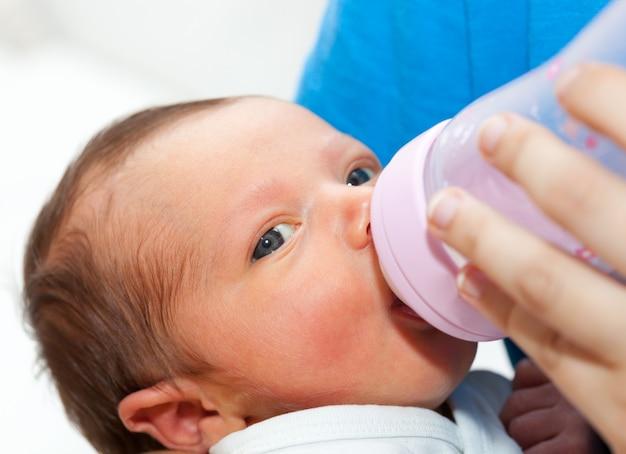 Schließen sie oben vom baby, das seine flasche trinkt