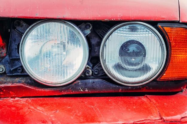 Schließen sie oben vom detail des vorderen scheinwerfers des alten roten autos