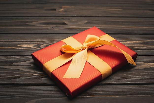 Schließen sie oben vom eleganten weihnachtsgeschenk, das mit goldenem farbband gebunden wird