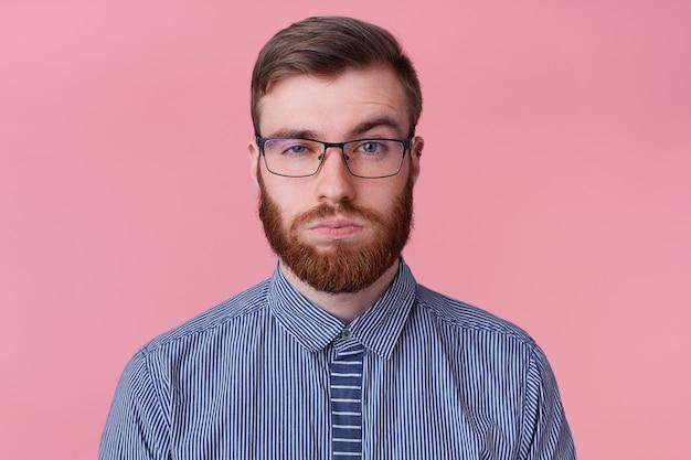 Schließen sie oben vom ernsten jungen attraktiven bärtigen mann in einem gestreiften hemd mit brille, eine augenbraue, die betrachtet wird, die kamera lokalisiert über rosa hintergrund betrachtet.