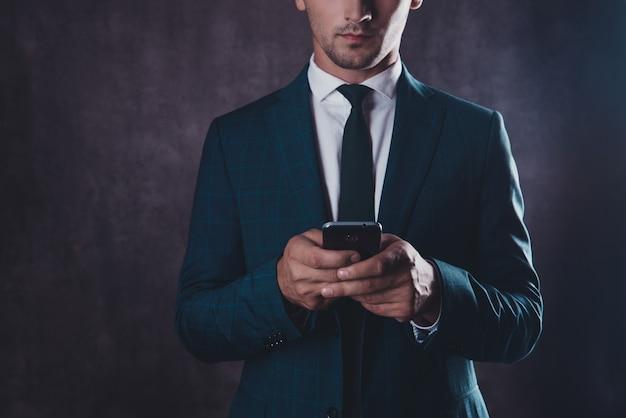 Schließen sie oben vom ernsten jungen erfolgreichen mann, der nachricht am telefon schreibt