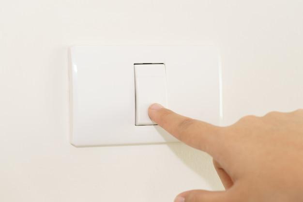 Schließen sie oben vom finger, der auf lichtschalter auf wand abstellt