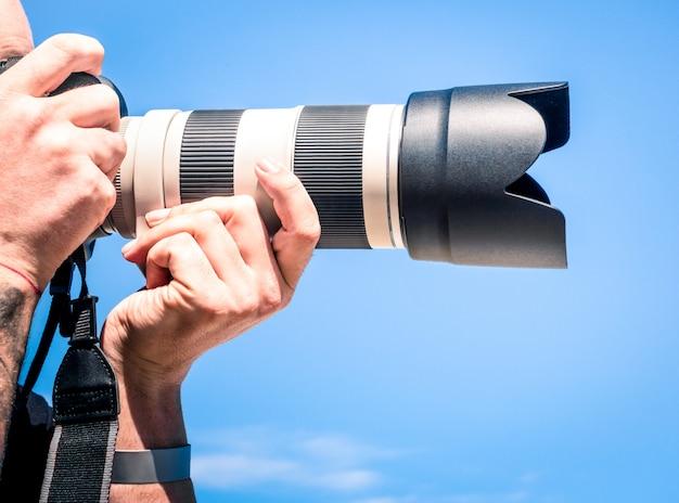 Schließen sie oben vom fotografen, der foto mit zoomobjektiv macht