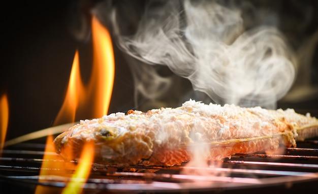 Schließen sie oben vom gegrillten fischfutter der meeresfrüchte mit salz auf dem grillfeuer und -rauch