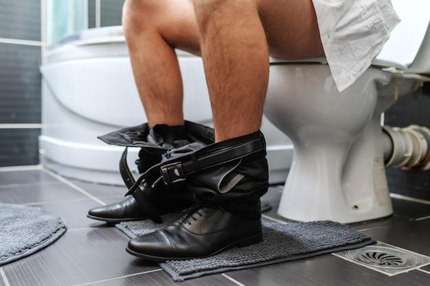 Schließen sie oben vom geschäftsmann, der auf toilette in der toilette am morgen sitzt.