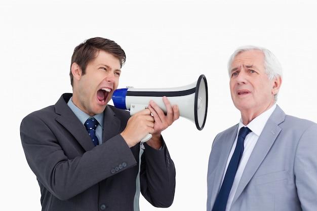 Schließen sie oben vom geschäftsmann mit dem megaphon, das an seinem chef schreit